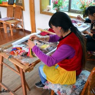 Donna Naxi che ricama con la seta